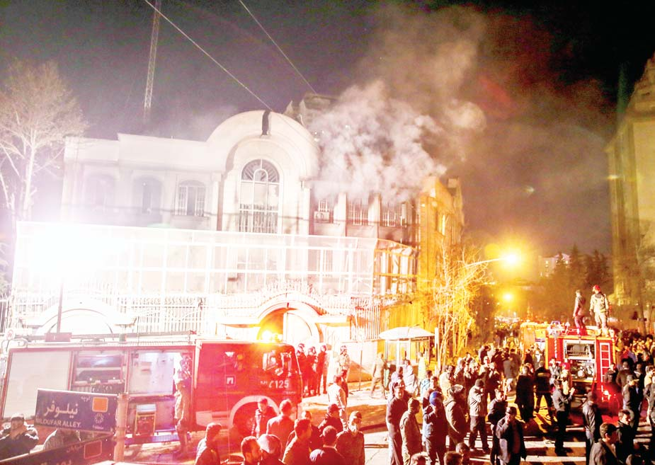 Smoke rises as Iranian protesters set fire to the Saudi embassy in Tehran on Jan 3. (AP)