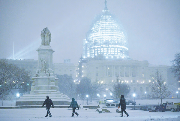 Pedestrians are seen in front of the US Capitol in Washington, DC, as snow continues to fall on Jan 22. A monster blizzard threatening the US East Coast slammed into Washington on Jan 22, blanketing the nation's capital in snow as offi cials urged millions in the storm's path to seek shelter, warning the worst was yet to come. (AFP)