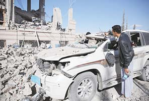 A man inspects his car damaged by Saudi-led airstrikes in Sanaa, Yemen on Jan 8. (AP)