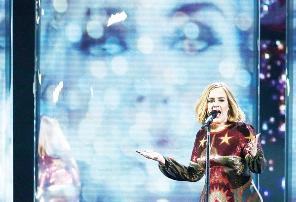 British singer Adele performs on stage during the Brit Awards 2016 in London on Feb 24. (Inset): Singer Adele holds her Best British Female Solo Artist award onstage at the Brit Awards 2016 at the 02 Arena in  London, on Feb 24. (AFP/AP)