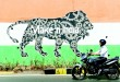 An Indian motorist rides past a wall bearing the image of the mascot for  'Make in India Week' in Mumbai on Feb 12. Over 190 companies and 5,000 delegates from 60 countries, are due to take part in the first 'Make in India' week to be held in Mumbai from Feb 13-18. (AFP)
