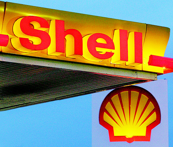 This file photo shows company logos and signage displayed at a Shell petrol station in east London. Royal Dutch Shell on Feb 4 announced an 87-percent plunge in annual net profits on slumping oil prices. The Anglo-Dutch group reported profit after tax of $1.94 billion (1.75 billion euros) for 2015, compared with almost $15 billion the previous year, Shell said in a statement. (AFP)