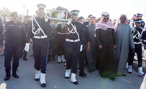 Remains of martyr Turki Mohammad Al-Enezi being carried by colleague policemen for burial.