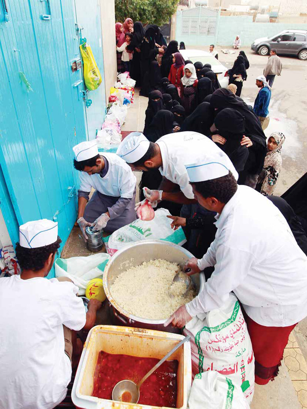 Yemeni volunteers distribute food to poor families as part of an initiative organised by a local charity in the capital Sanaa, on Feb 24. (AFP)