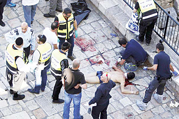 Israeli emergency services and police stand around the body of an alleged Palestinian attacker in Jerusalem on Feb 19. The Palestinian stabbed two officers in Jerusalem before he was shot and killed, police said. (AP)