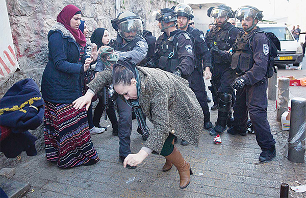 An Israeli border policeman pushes a Palestinian woman away as Israeli police clear a street following an attack by three. Palestinian assailants at Damascus Gate