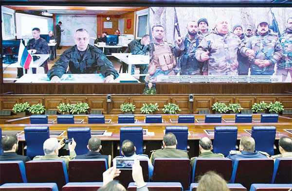 Lt-Gen Sergei Rudskoy of the Russian Military General Staff, speaks to the media in Moscow, Russia, on Feb 27. A top military official says Russia has halted all airstrikes in areas of Syria where armed groups, including government forces, said they would abide by a cease-fire. The screen shows, (at right), a commander of the opposition unit that pledged adherence to the cease-fire; (at left), Lt-Gen Sergei Kuralenko at Hemeimeem airbase in Syria. (AP)
