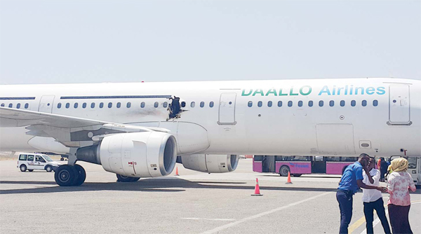 In this photo taken on Feb 2, 2016, a hole is seen in a plane operated by Daallo Airlines as it sits on the runway of the airport in Mogadishu, Somalia. A gaping hole in the commercial airliner forced it to make an emergency landing at Mogadishu's international airport late Tuesday officials and witnesses said. (AP)