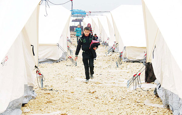 Displaced Syrians fl eeing areas in the northern embattled province of Aleppo, walk past tents at the Bab al-Salama camp, set up outside the Syrian city of Azaz on Syria's northern border with Turkey on Feb 12. (AFP