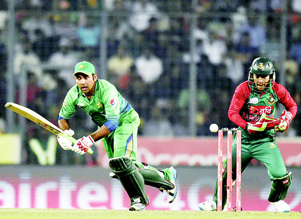 Pakistan cricketer Sarfraz Ahmed (left), plays a shot as Bangladesh wicketkeeper Mushfiqur Rahim (right), looks on during the Asia Cup T20 tournament match between Bangladesh and Pakistan at The Sher-e-Bangla National Cricket Stadium in Dhaka on March 2. (AFP)