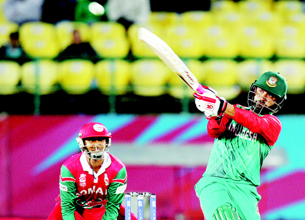 Bangladesh's Tammim Iqbal hits a '6' to complete a century (100 runs) during the qualifying match for the World T20 cricket tournament between Bangladesh and Oman at the Himachal Pradesh Cricket Association Stadium in Dharamsala on March 13. (AFP)