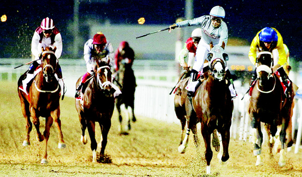 Victor Espinoza (2nd right), celebrates after leading California Chrome to win the Dubai World Cup race, during the Dubai World Cup horse racing event on March 26 at the Meydan racecourse in the United Arab Emirate of Dubai. (AFP)