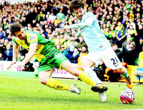 Manchester City's David Silva (right), and Norwich City's Wesley Hoolahan battle for the ball during the English Premier League soccer match at Carrow Road, Norwich, England, on March 12. (AP)