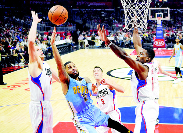 Denver Nuggets guard D.J. Augustin (second from left), shoots as Los Angeles Clippers center Cole Aldrich (left), guard Pablo Prigioni (second from right), of Argentina and forward Jeff Green defend during the first half of an NBA basketball game on March 27 in Los Angeles. (AP)