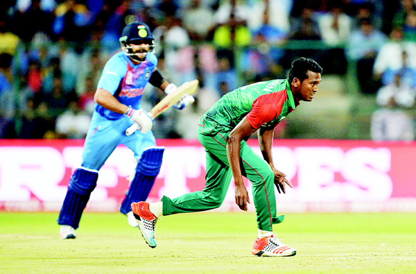 India's batsman Virat Kohli (left), takes a run while Bangladesh bowler Al Amin Hossain misses a catch during the World T20 cricket tournament match between India and Bangladesh at The Chinnaswamy Stadium in Bangalore on March 23. (AFP)