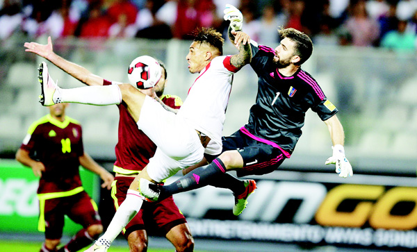 Peru's Paolo Guerrero (left), fights for the ball with Venezuela's goalkeeper Alain Baroja during a 2018 World Cup qualifying soccer match in Lima, Peru, March 24. (AP)