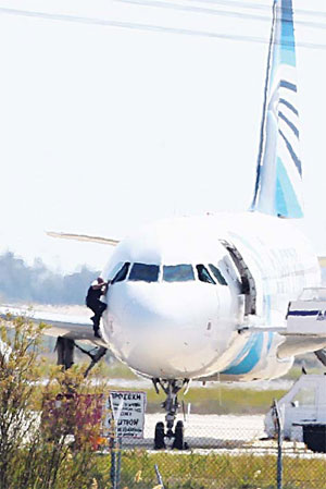 A man, leaves the hijacked aircraft of EgyptAir from the pilot's window after landing at Larnaca Airport on March 29. An EgyptAir plane was hijacked while fl ying from the Egyptian Mediterranean coastal city of Alexandria to the capital, Cairo. (AP)