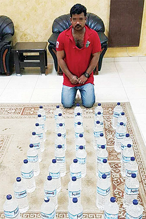 The Indian man with the seized 30 bottles of locally-manufactured liquor.