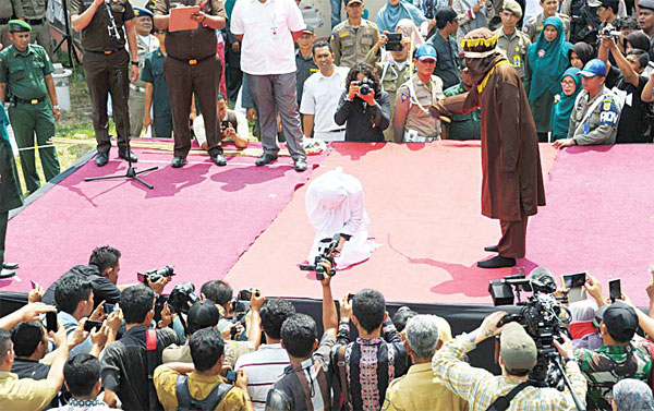 A sharia policeman (right), canes a woman (center-kneeling) for breaking Islamic law during a public punishment in Banda Aceh on March 1. The woman, who had been caught spending time with a young man in a room, was one of 18 people publicly caned Tuesday for breaking Islamic law in Indonesia's Aceh province. (AFP)