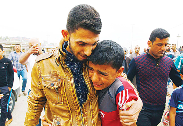 Iraqi relatives and friends mourn on March 26 in Iskandariyah, a town about 40 kms (25 miles) south of the capital Baghdad, during the funeral of some of the victims of a suicide bomb attack in a nearby village the day before. (AFP)