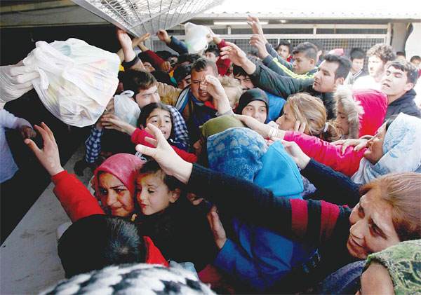 Refugees and migrants reach for food packages provided by humanitarian workers, at the transit center for refugees near northern Macedonian village of Tabanovce on the border with Serbia on March 28. More than 1,000 refugees and migrants remain stranded in northern Macedonia since earlier this month, after a string of countries shut down the Balkan route which migrants sued to go from Greece to central and northern Europe. (AP