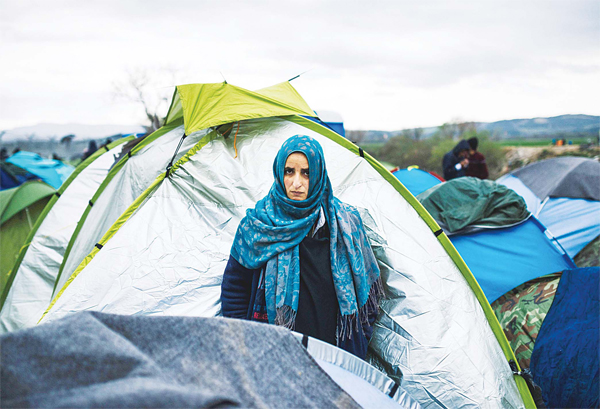 A woman stands in front of her tent at a makeshift camp at the Greek-Macedonian border