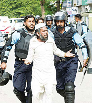 Pakistani riot policemen arrest a supporter of executed Islamist Mumtaz Qadri during an anti-government protest near the parliament building in Islamabad on March 28. (AFP)