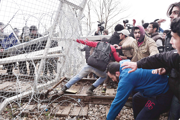 Migrants try to break through a border fence into Macedonia near the Greek village of Idomeni, on Feb 29, where more than 7,000 people are stranded, as anger mounted over travel restrictions on migrants.