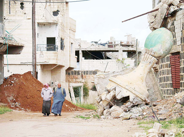 Syrian elderly men walk past a damaged mosque in a rebel-held area of Daraa, in southern Syria, on March 28. (AFP)