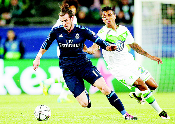 Real Madrid's Gareth Bale (left), is chased by Wolfsburg's Luiz Gustavo during the Champions League first leg quarter-final soccer match between VfL Wolfsburg and Real Madrid in Wolfsburg, Germany, on Apirl 6. (AP)
