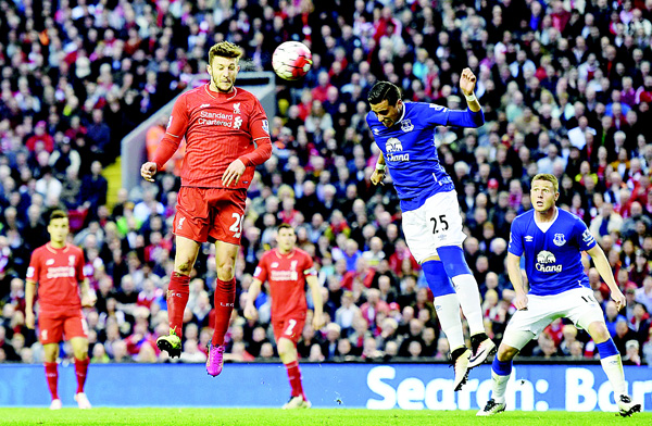 Liverpool's English midfielder Adam Lallana (left), heads the ball toward goal during the English Premier League football match between Liverpool and Everton at Anfield in Liverpool, north west England on April 20. (AFP)