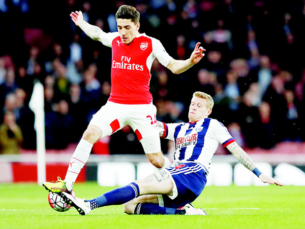 Arsenal's Hector Bellerin (left), competes for the ball with West Bromwich Albion's Jason McClean during the English Premier League soccer match between Arsenal and West Bromwich Albion at the Emirates Stadium in London on April 21. (AP)