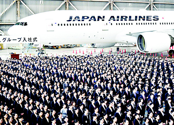 New employees of Japan Airlines Group attend an entrance ceremony at a hangar in Tokyo's Haneda Airport on April 1, 1,460 new employees of JAL Group attended the ceremony. (AFP)
