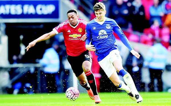 Manchester United's French striker Anthony Martial (left), tries to get in front of Everton's English defender John Stones (right) during the English FA Cup semifinal football match between Everton and Manchester United at Wembley Stadium in London on April 23. (AFP)
