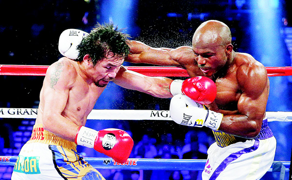 Manny Pacquiao (left), of the Philippines, tries to avoid a punch by Timothy Bradley during their WBO welterweight title bout on April 9, in Las Vegas. (AP)