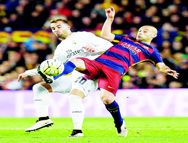 Barcelona's Argentinian defender Javier Mascherano (right), vies with Real Madrid's forward Jese Rodriguez during the Spanish League 'Clasico' football match FC Barcelona vs Real Madrid CF at the Camp Nou Stadium in Barcelona on April 2. (AFP)