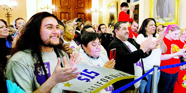 Supporters of a bill to raise California's minimum wage, celebrate outside the state Senate Chamber after the measure was approved by the Senate on March 31, in Sacramento, California. The bill, SB3, that will gradually raise California's minimum wage to a nation leading $15 an hour by 2022, was approved by both houses of the Legislature and sent to Gov Jerry Brown who said he will sign it. (AP)