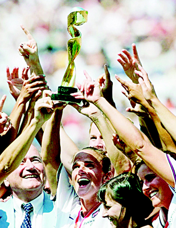 In this July 10, 1999, file photo, US women's soccer team captain Carla Overbeck (center), and other members of the US team celebrate with the trophy after defeating China 5-4 in an overtime penalty shootout in the Women's World Cup final at the Rose Bowl in Pasadena, California. (AP)