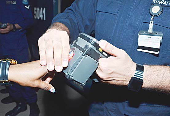 A Kuwaiti police officer scans the finger of an expatriate during a security campaign in Mahboula Wednesday evening