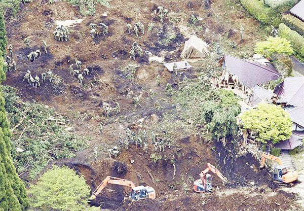 Rescuers search for missing persons at the site of a landslide in Minamiaso, Kumamoto prefecture, Japan on April 18.