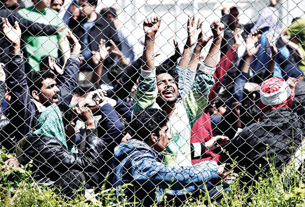 Men hold their hands up behind a chain link fence as Pakistani and Afghan migrants protest inside the Moria detention center in Mytilene on the Greek island of Lesbos