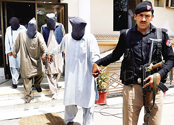 A police offi cer escorts suspects who allegedly killed Sikh lawmaker Sardar Soran Singh after a press conference in Peshawar, Pakistan on April 25. (AP