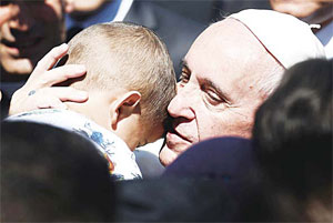 Pope Francis hugs a child at the Moria detention center in Mytilene on April 16.