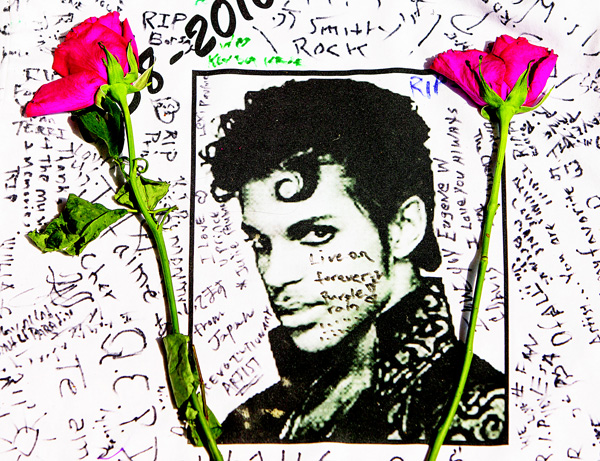 Flowers lay on a T-shirt signed by fans of singer Prince at a makeshift memorial place created outside Apollo Theatre in New York, on April 22. (AP)