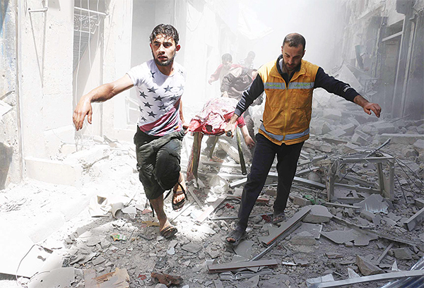 Syrian men carry a body on a stretcher amid the rubble of destroyed buildings following a reported air strike on the rebel-held neighbourhood of Al-Qatarji in the northern Syrian city of Aleppo, on April 29.