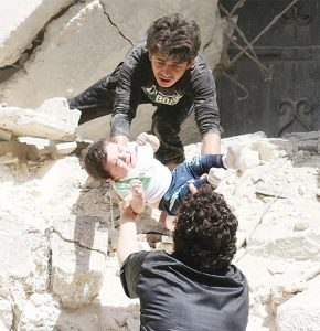 Syrians evacuate a toddler from a destroyed building following a reported air strike on the rebel-held neighbourhood of al-Kalasa in the northern Syrian city of Aleppo, on April 28. (AFP