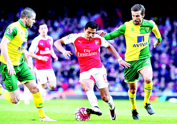 Arsenal's Chilean striker Alexis Sanchez (center), turns away from Norwich City's English midfielder Gary O'Neil (right), during the English Premier League football match between Arsenal and Norwich at the Emirates Stadium in London on April 30. (AFP)