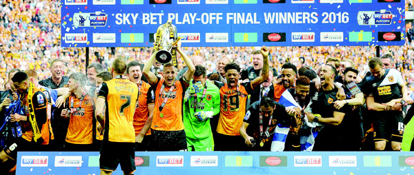 Hull City's English defender Michael Dawson (5th left), lifts the trophy during the presentation after Hull City won the English Championship play-off final football match between Hull City and Sheffield Wednesday at Wembley Stadium in London on May 28. Hull City secured promotion to the Premier League with a 1-0 victory in the Championship play-off final at Wembley against Yorkshire rivals Sheffield Wednesday. (AFP)