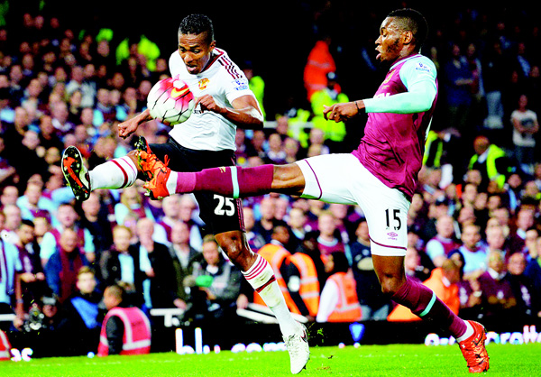 Manchester United's Ecuadorian midfielder Antonio Valencia (Left), vies with West Ham United's Senegalese striker Diafra Sakho during the English Premier League football match between West Ham United and Manchester United at The Boleyn Ground in Upton Park, in east London on May 10. (AFP)