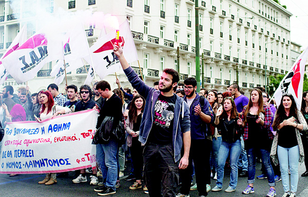 A protester holds a flare as other chant anti-austerity slogans in front of the Greek parliament in central Athens, on May 6. Services have ground to a halt in Greece as workers start a three-day general strike protesting new bailout austerity measures they say will further decimate incomes, in a sign of growing discontent with the left-led coalition government. (AP)